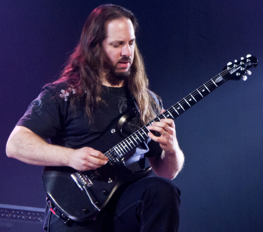 John Petrucci executa técnica da palhetada alternada, durante show do Dream Theater