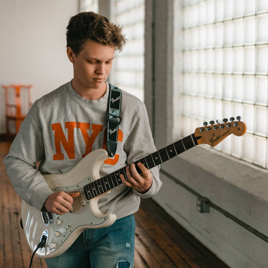 Guitarrista principiante entrenando ejercicios para mejorar al mano izquierda