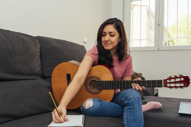 Mulher sentada no sofá segura violão e anota notas musicais