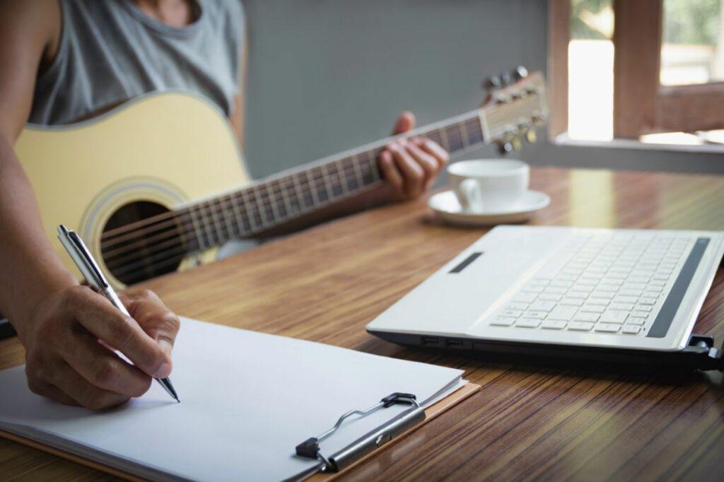 Músico segura violão e anota notas musicais na partitura