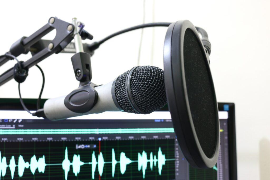 Microfone e programa de computador prontos para a gravação de um podcast