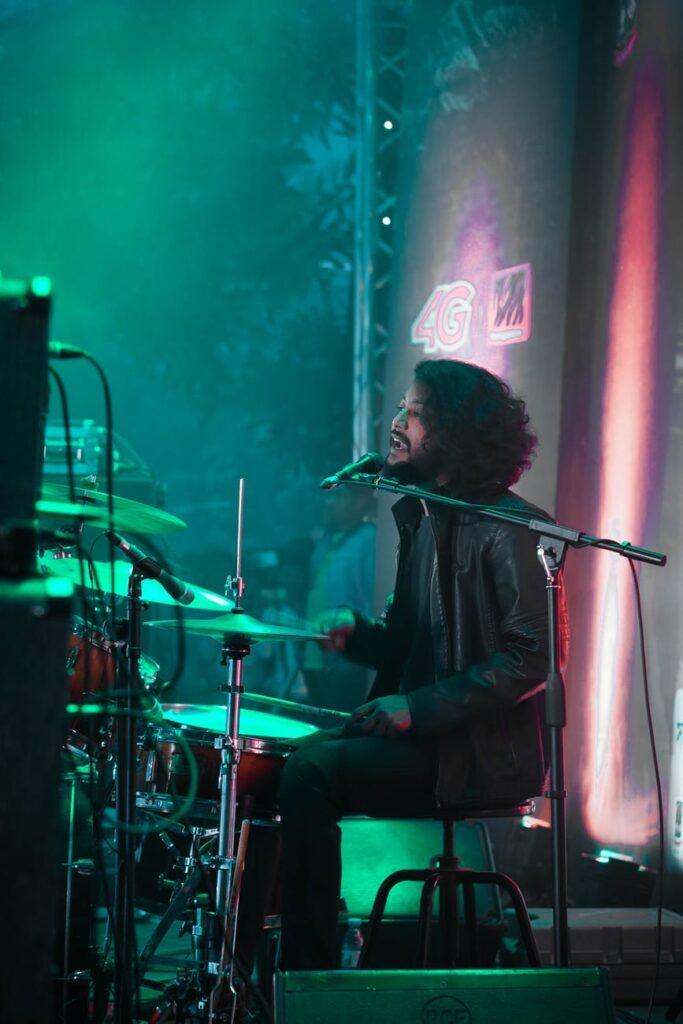 Baterista toca e canta ao mesmo tempo, durante apresentação