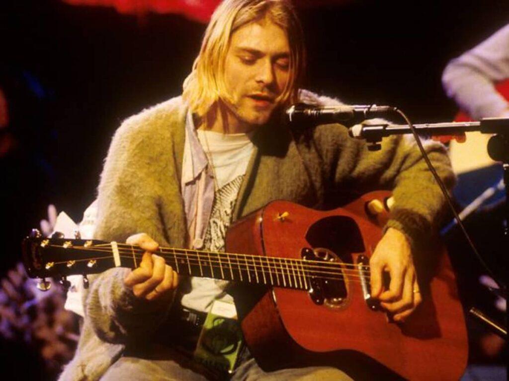 Kurt cobain tocando la guitarra y cantando al mismo tiempo