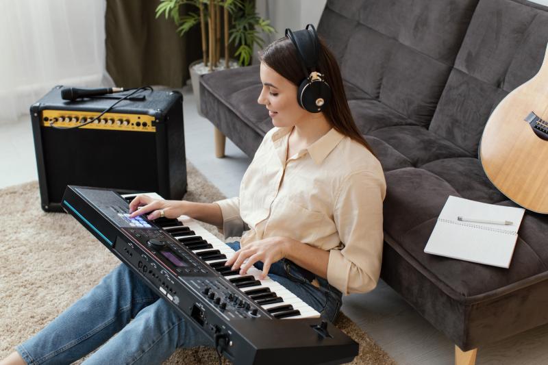 Mulher toca teclado sentada no chão