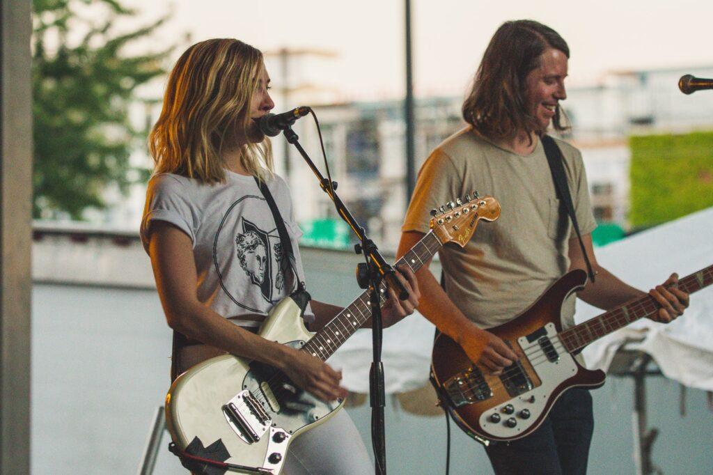 Mulher guitarrista e homem baixista fazendo um som,. Ela consegue tocar e canta ao mesmo tempo