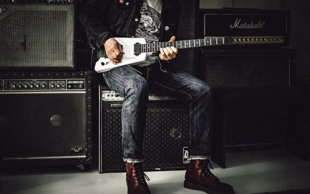 Guitarrista sentado diante de uma parede de amplificadores