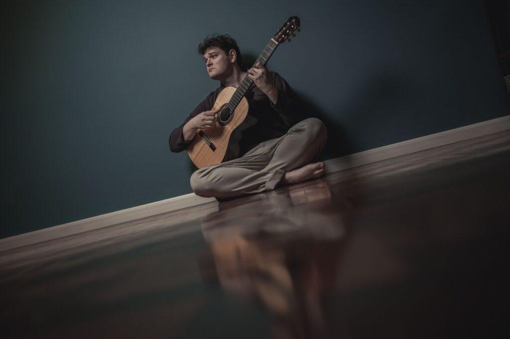 Lucas Telles com violão em mãos e sentando no chão de uma sala