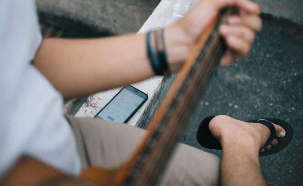 Homem toca violão e consulta um dos aplicativos de partitura no smartphone