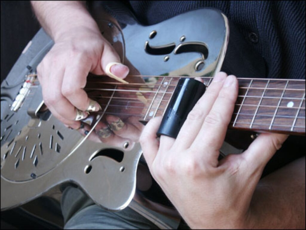 Homem toca slide em violão com cordas de aço