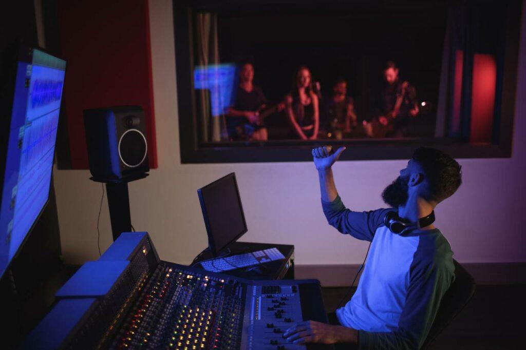 Técnico de áudio trabalhando em estúdio, ambiente perfeito para entender o que é o som