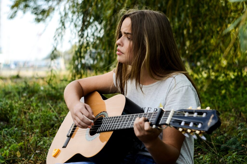 Mulher tocando violão, sentada na grama e usando capotraste