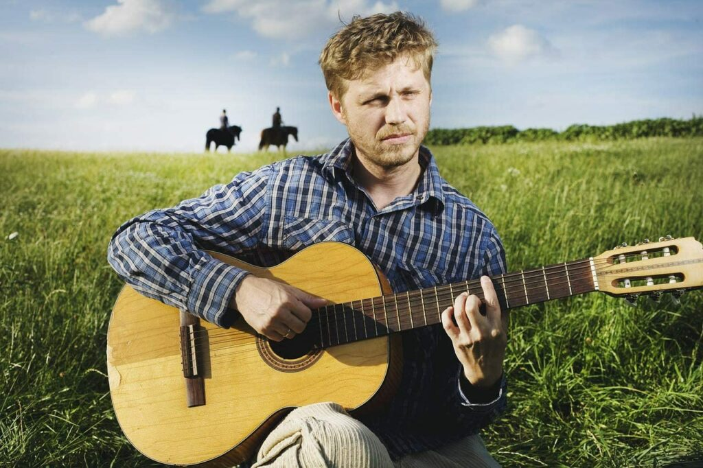 Homem sertanejo toca violão no campo