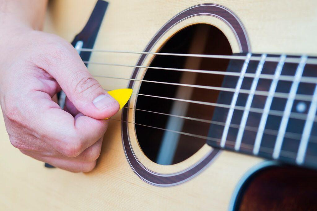 Close na mão de um homem tocando violão com palheta
