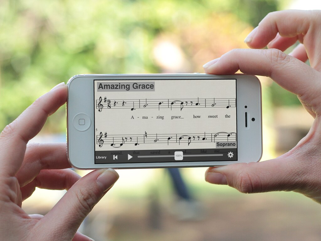 Mãos femininas seguram um telefone que funciona o MuseScore, um dos aplicativos de partitura mais completos