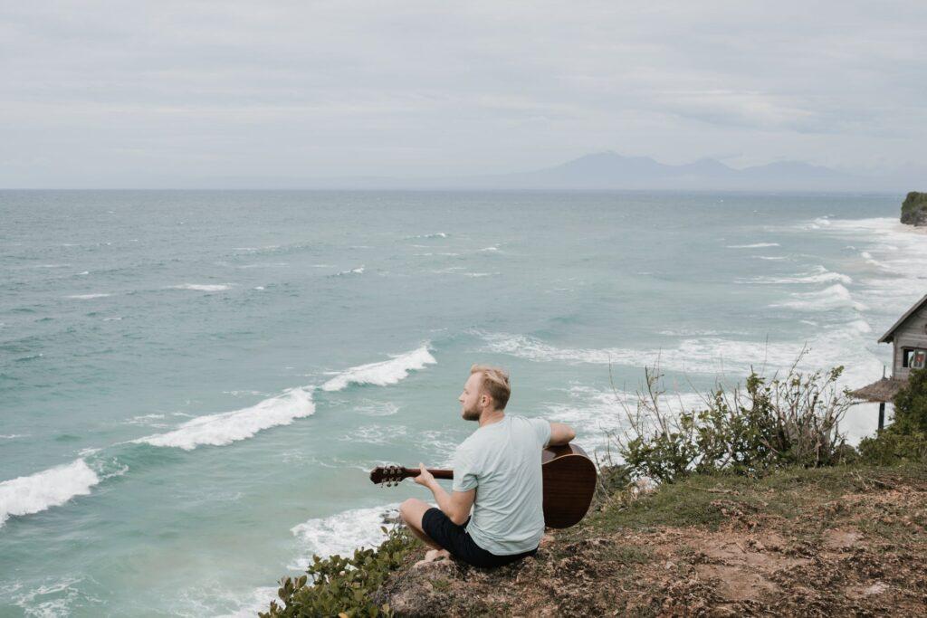 Músico toca violão de frente pro mar