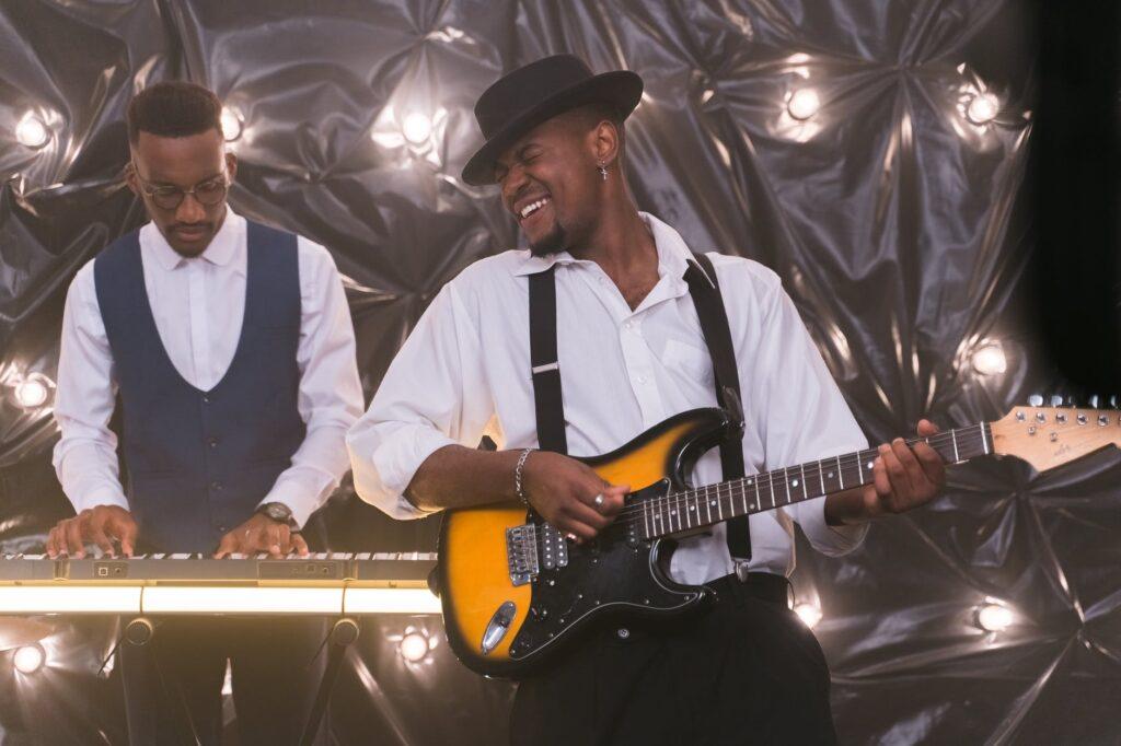 Tecladista e guitarrista fazendo improvisação musical durante um show