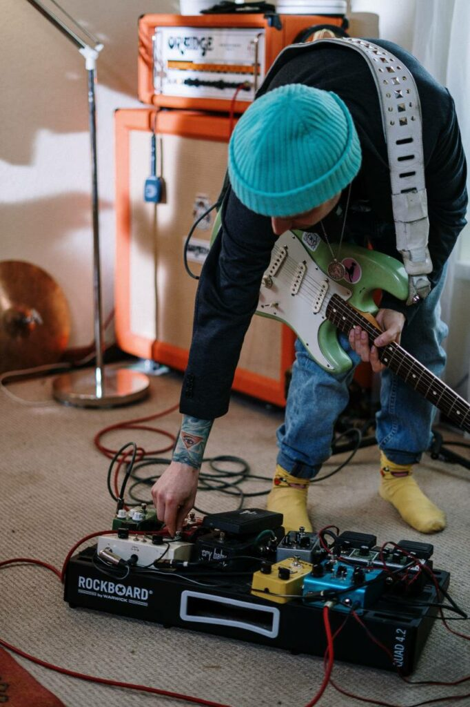 Guitarrista regula pedal no set de pedais montado no pedalboard