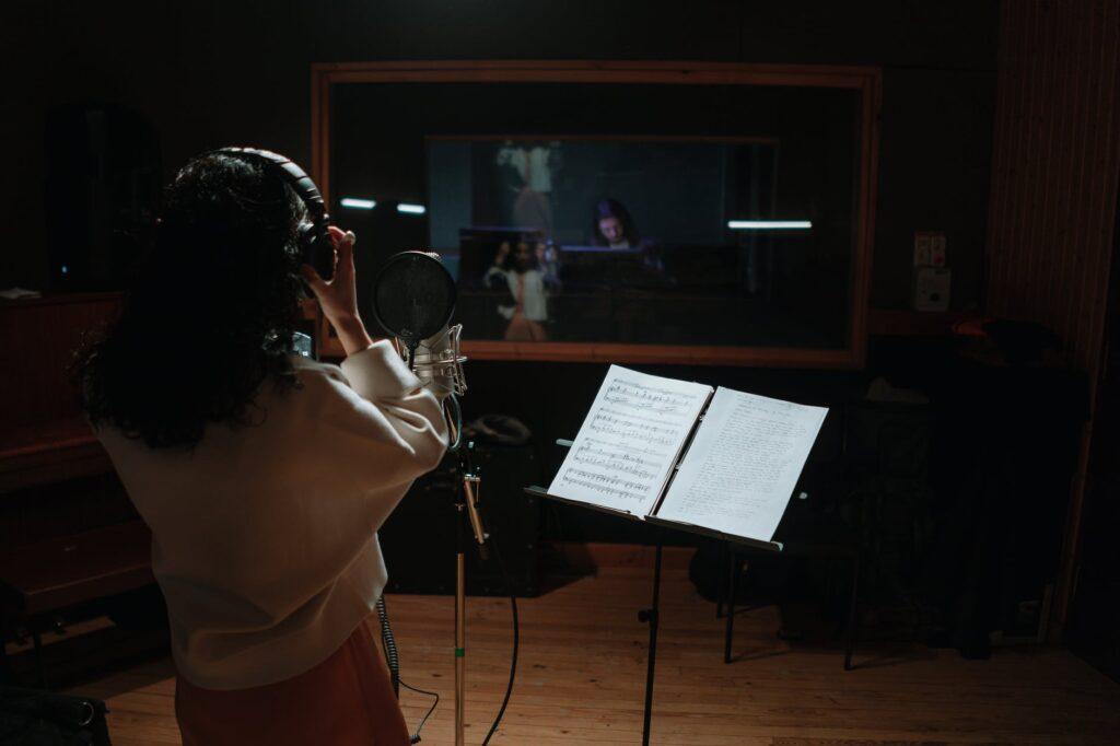 Cantora gravando voz em estudio e produtor trabalhando na mesa de som