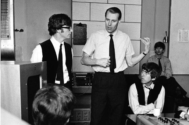 O produtor musical George Martin durante sessão de gravação com os Beatles.