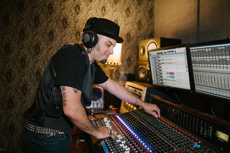 Produtor musical operando mesa de som, durante gravação
