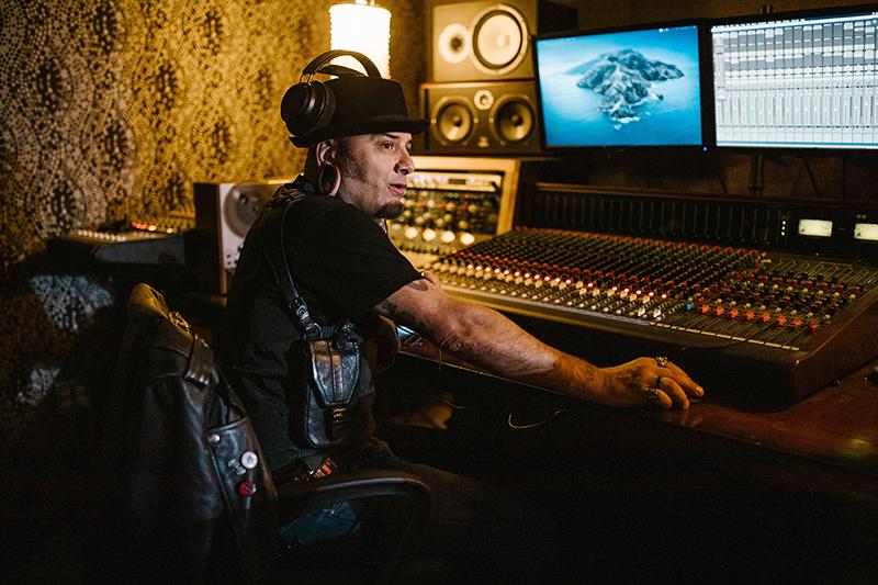 Produtor musical sentado à mesa de som em estúdio de gravação