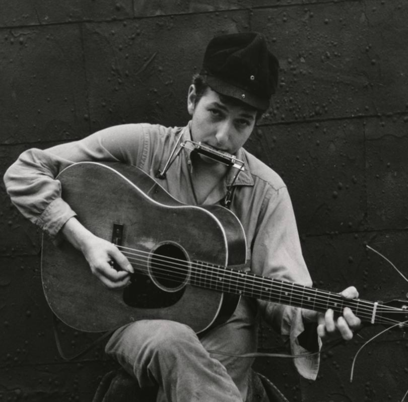 Um jovem Bob Dylan tocando violão e gaita