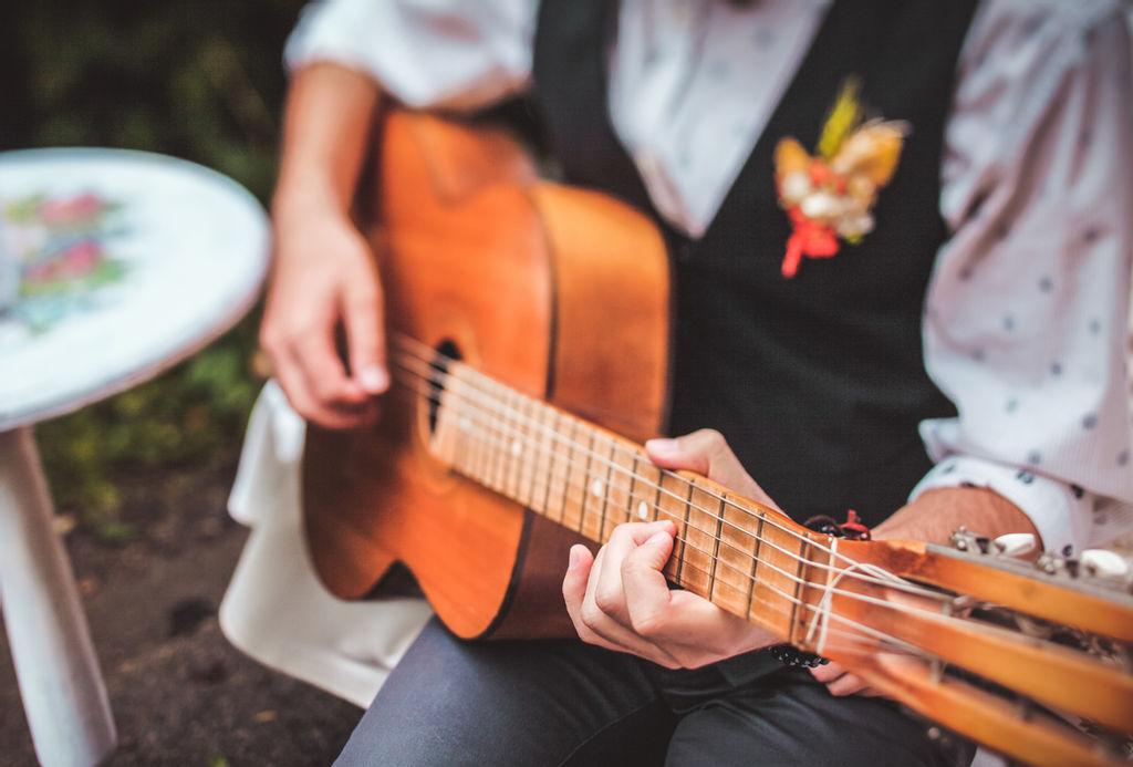 Músico sentado tocando músicas para casamento no violão