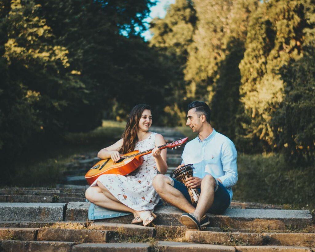 Casal de namorados sentados no degrau de uma escada; ela toca violão e ele toca instrumento de percussão