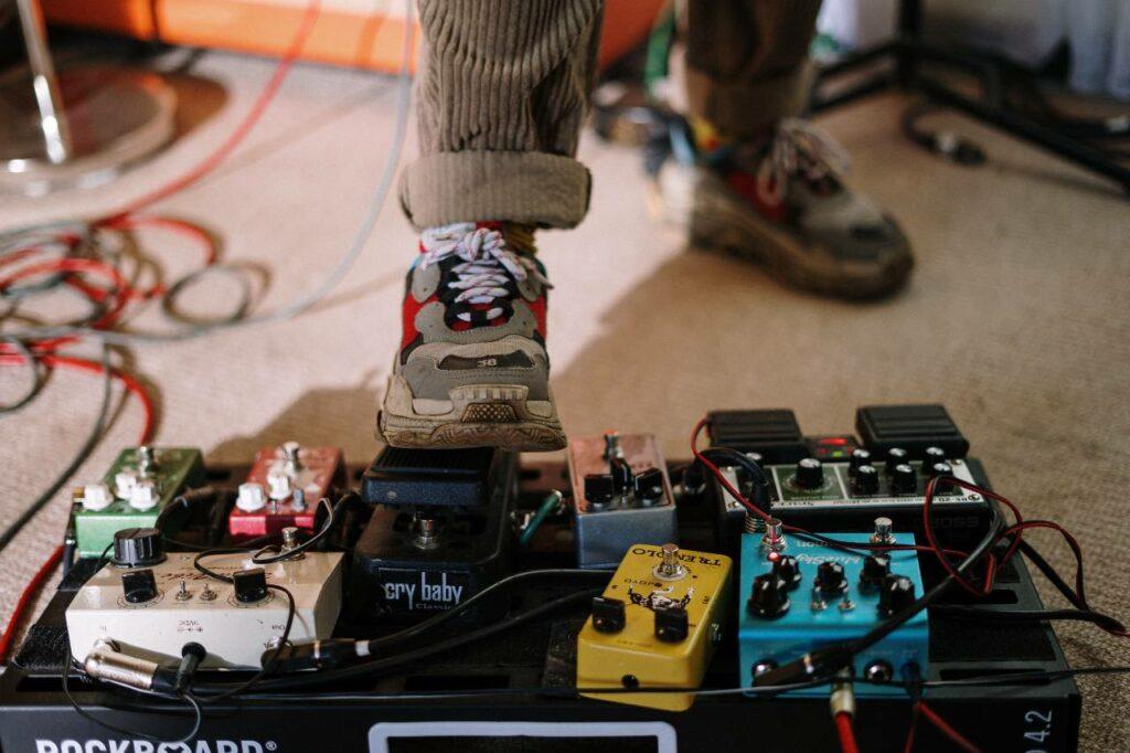 Set de pedais montado, o guitarrista pisa no pedal Cry Baby