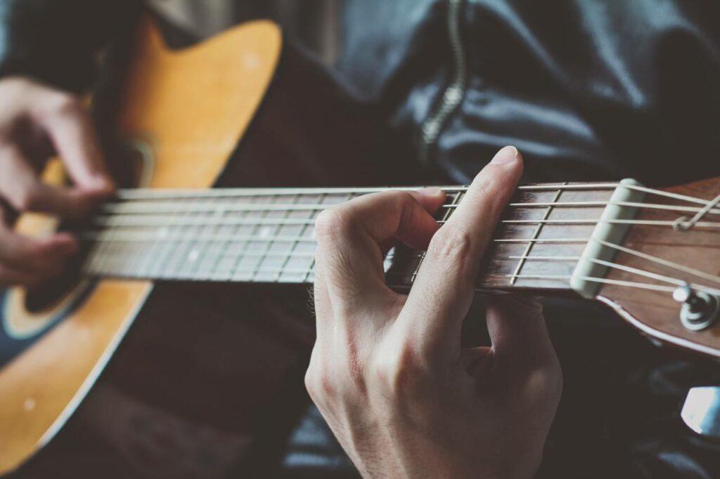 Homem toca música com pestana no violão