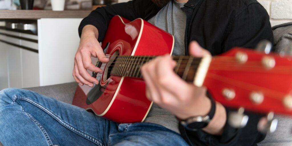 Músico toca dedilhados no violão para iniciantes