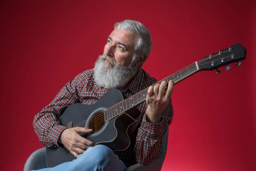Homem idoso não se importa com gastar tempo para aprender a tocar violão, ou seja, estuda a vida toda e todos os dias