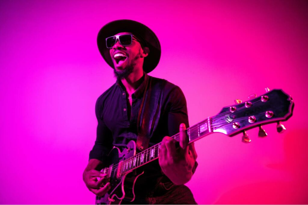 Guitarrista negro toca músicas com pestana na guitarra