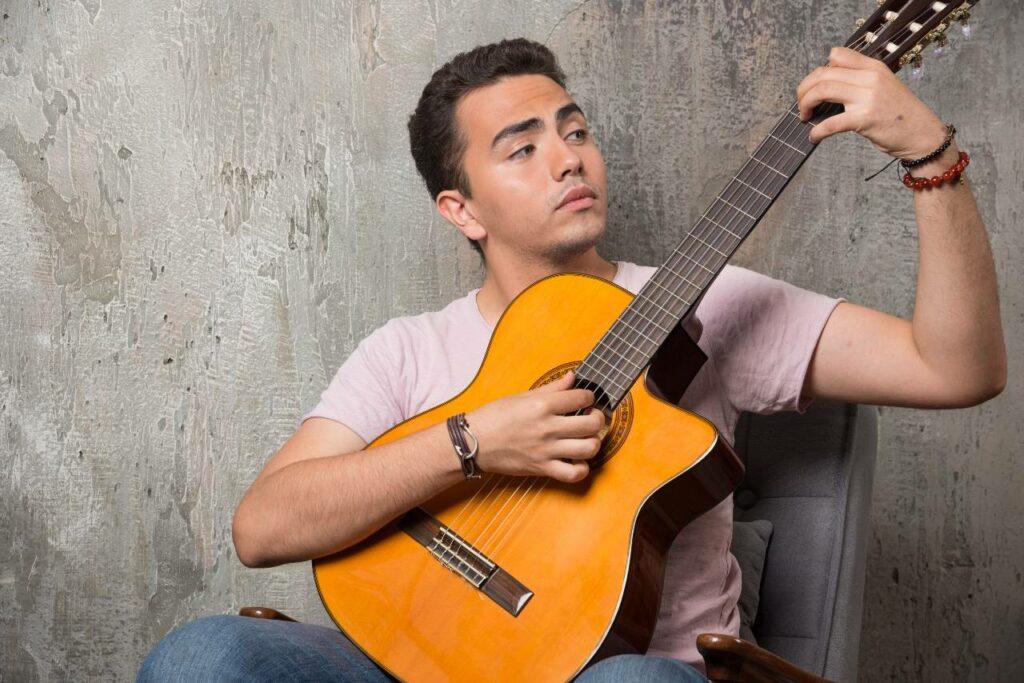 Músico jovem tocando dedilhado no violão