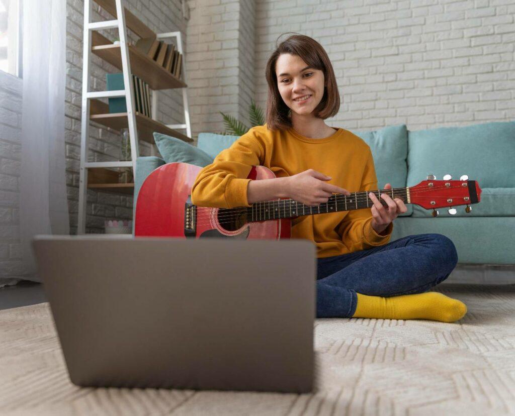 Jovem mulher toca o acorde de Dó maior no violão e executa músicas sem pestanas