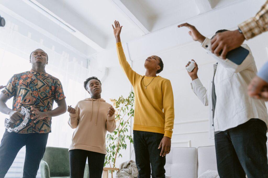 Jovens negros cantam música gospel, durante culto cristão
