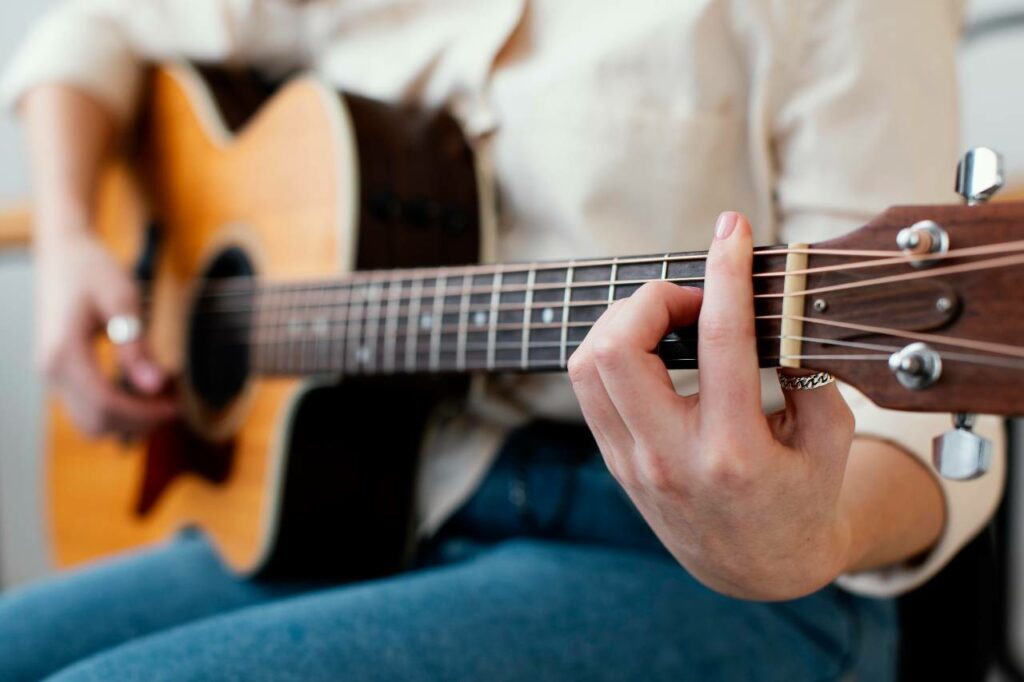 Mulher tocando músicas com pestana em um violão acústico e com cordas de aço