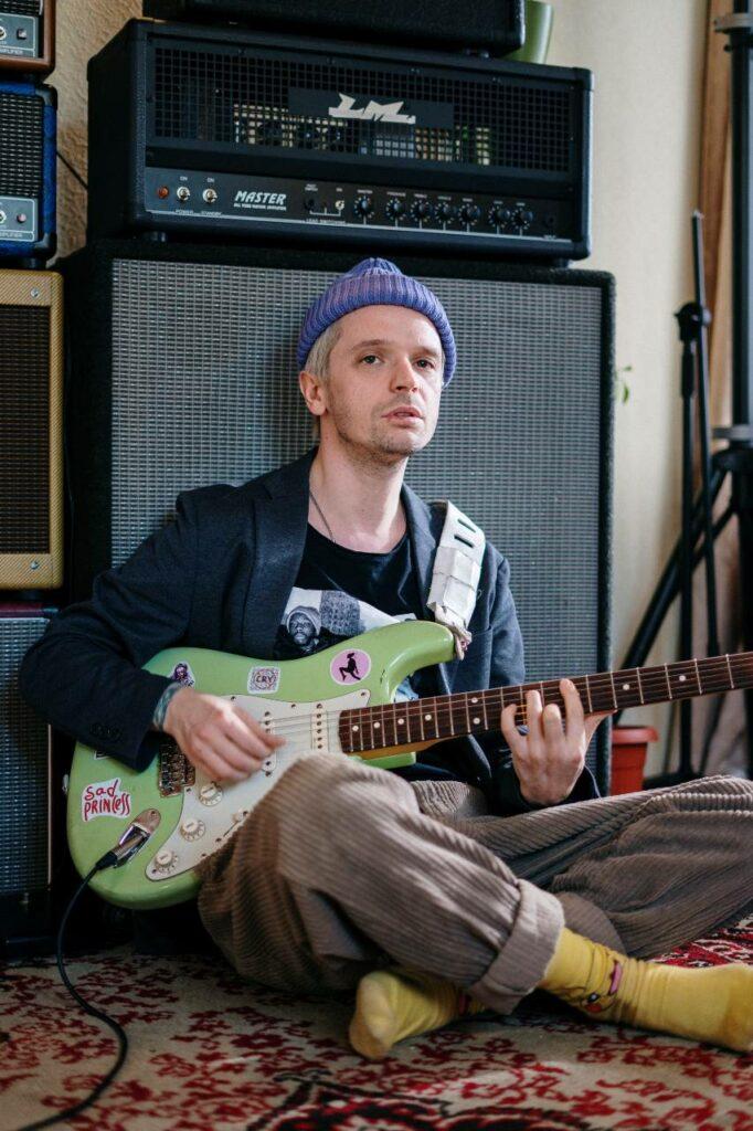Guitarrista sentado ao chão e encostado em um amplificador de guitarra valvulado