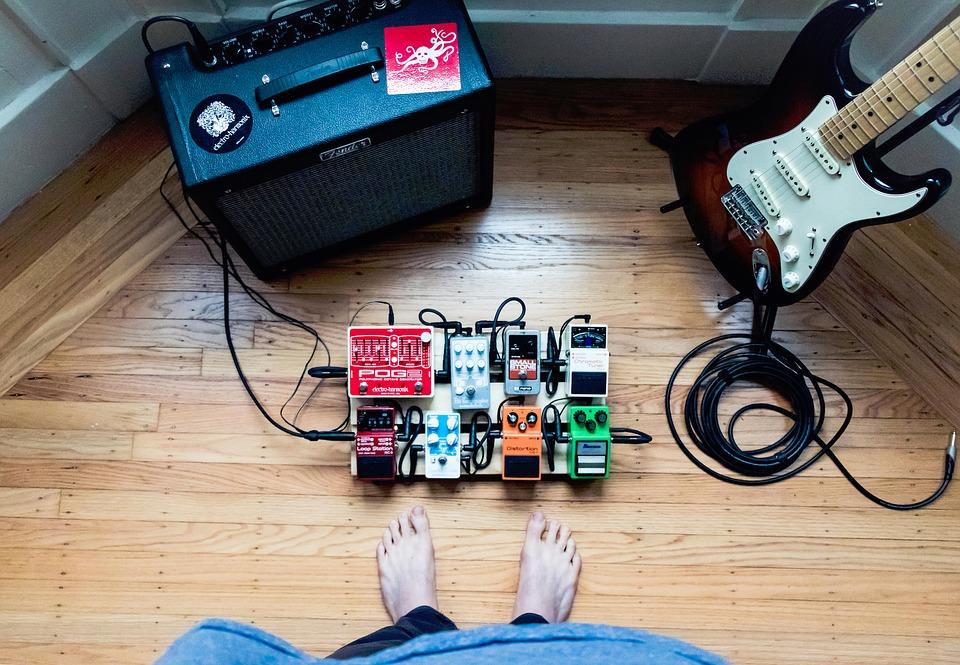 Guitarrista observa seu set completo: pedalboard, guitarra, amplificador e cabos