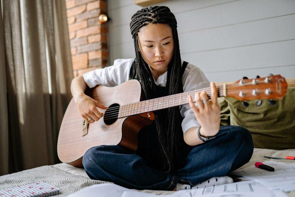 Mulher asiática faz progressão de acordes no violão