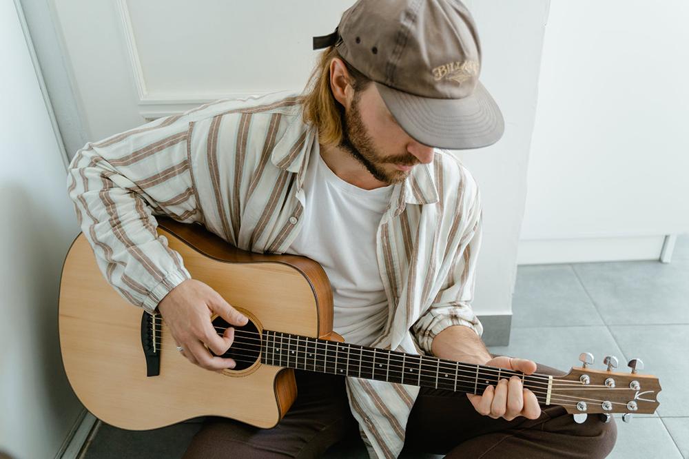 Músico tocando os dedilhados mais famosos no violão
