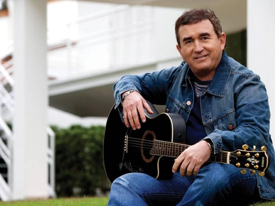 Cantor Amado Batista sentando com violão em mãos, pronto para tocar cifras de música brega