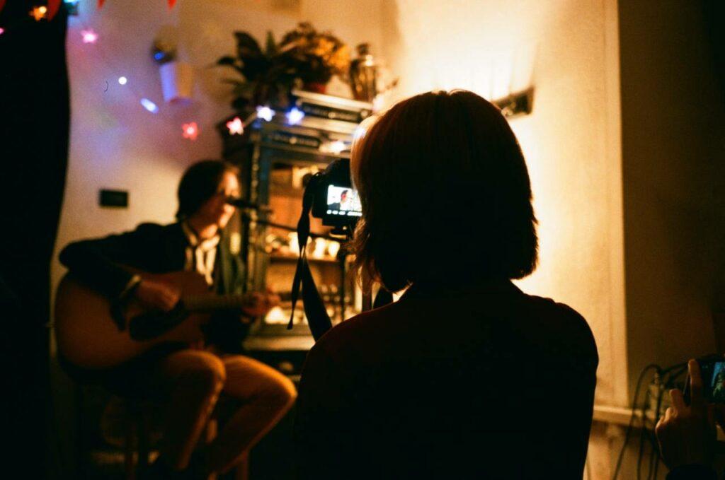 Mulher filma músico tocando no formato voz e violão