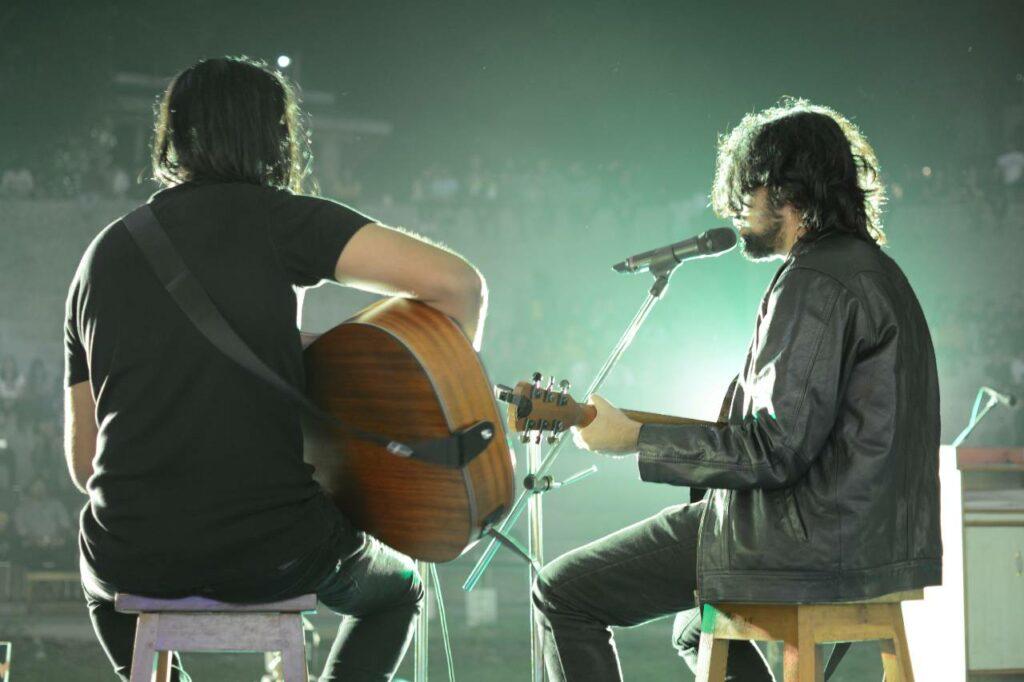 Dois músicos tocando com equipamentos para voz e violão