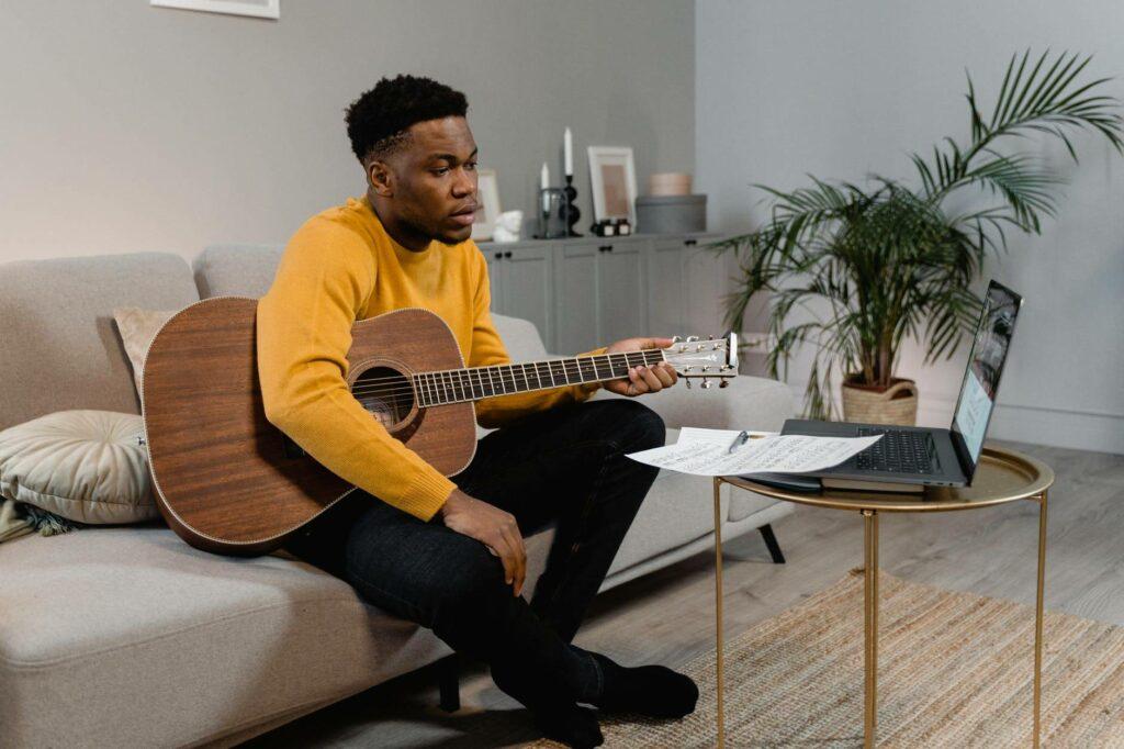 Homem negro assista aula de violão por meio de um notebook