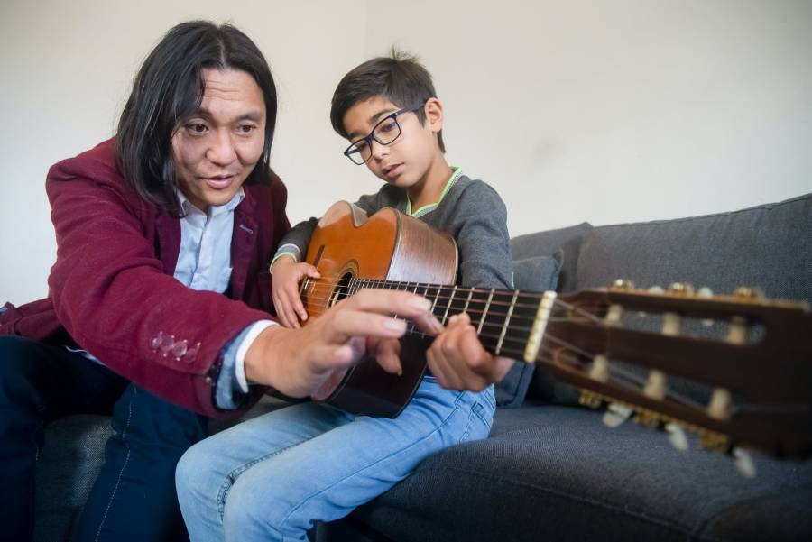 Professor ensina aluno a fazer acorde no violão