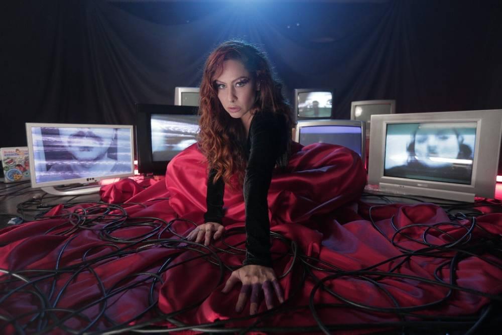 Pitty de vestido vermelho e sentada com TVs ao redor