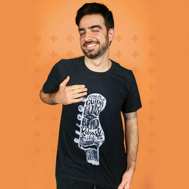 Instrutor Caico Antunes vestindo uma camisa preta com um headstock de guitarra estampado