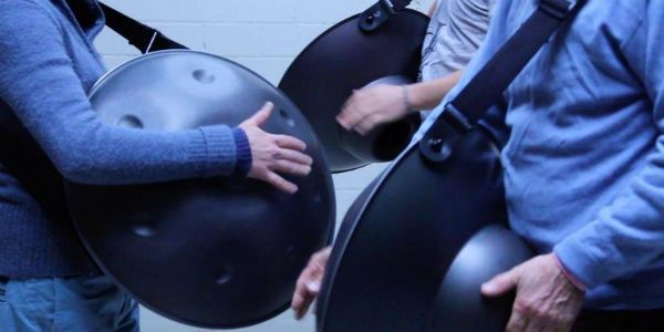 personas cargando un hang drum