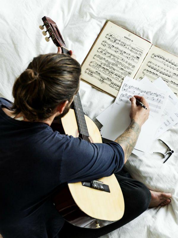 Músico segura o violão e escreve a música em uma partitura